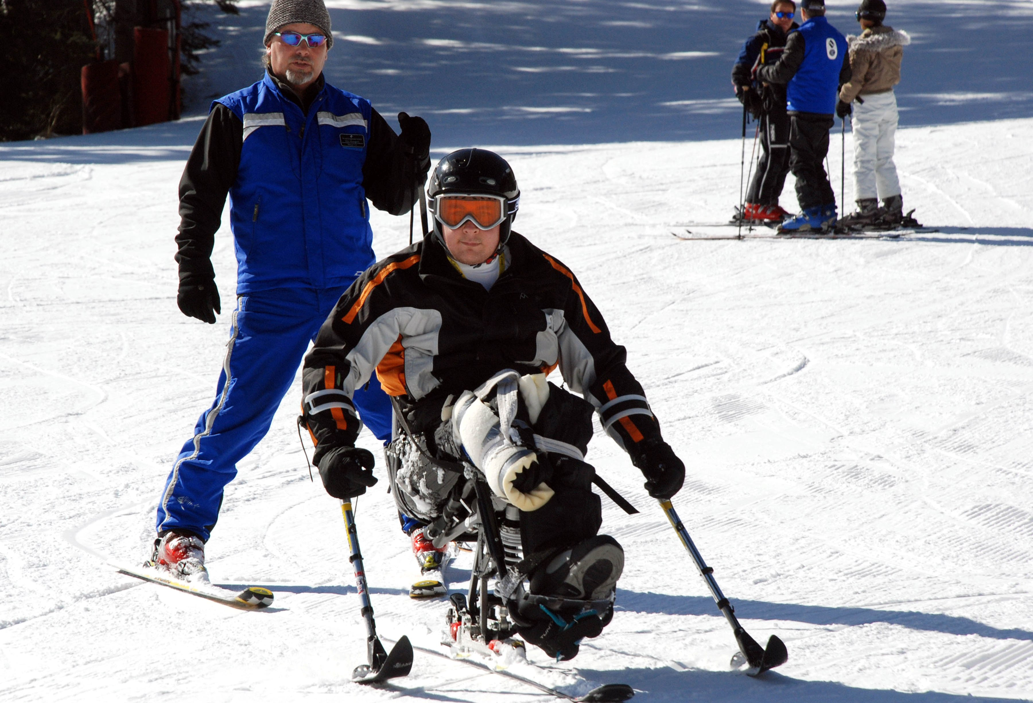 Sgt. Anthony Larson, his adaptive ski instructor close behind, skis down the beginner's hill in his mono-ski March 9, 2007 in Vail, Colo. Larson lost his right leg below the knee while serving in Iraq. The private mono-ski lesson is part of the Vail Veterans Program's winter sports clinic. Defense Dept. photo by Samantha L. Quigley